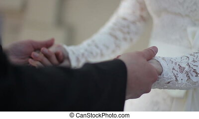 groom holds the bride's hands and gently stroking their
