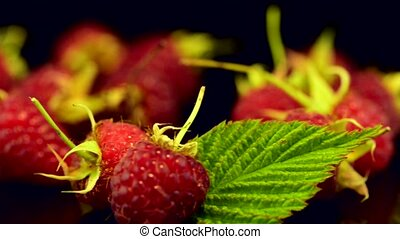 Fresh raspberries on black reflective background