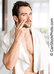 Male Skin Care - Male applying moisturizer to her face in...
