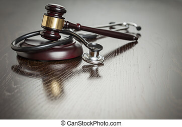 Gavel and Stethoscope on Reflective Table - Gavel and...