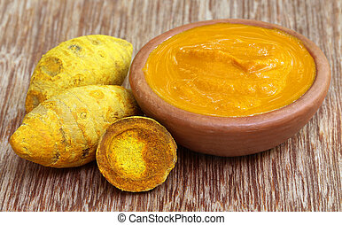 Dried turmeric with paste on wooden surface