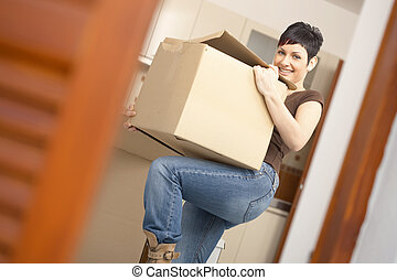 Young woman lifting cardboard box - Woman lifting cardboard...