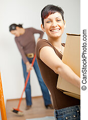 Young woman with cardboard box - Woman lifting cardboard box...
