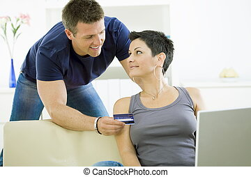 Couple paying with credit card - Happy couple paying with...