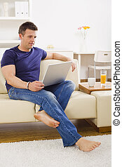 Man browsing internet on laptop computer at home.
