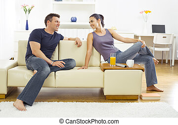 Young couple at home - Happy young couple sitting on sofa at...