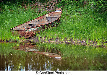 rusty old rowboat - Rusty row boat with pond water...