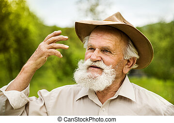 Old farmer - Portrait of old farmer with beard and hat in...