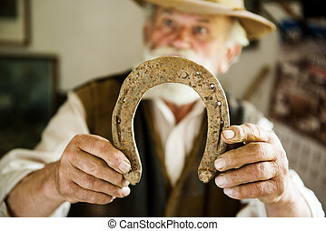 Old farmer with beard and hat holding horseshoe