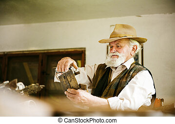 Old farmer with beard and hat in his workroom