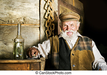 Old man - Portrait of old farmer with beard and hat holding...