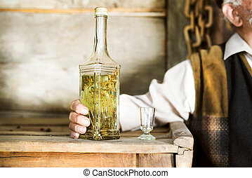 Old man - Close-up of of bottle of herbal spirit held by an...