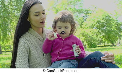 Soap Bubbles - Mother and child on the lawn blowing soap sud