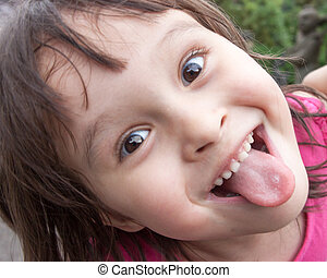 Young girl sticking out tongue while making funny face -...