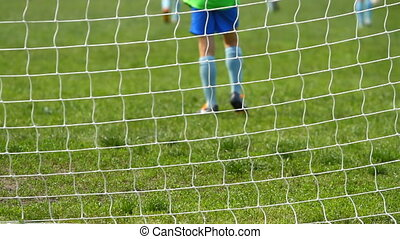 Children soccer game from behind goal net