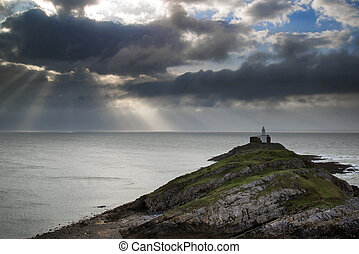 Lighthouse on headland with sun beams over ocean landscape...
