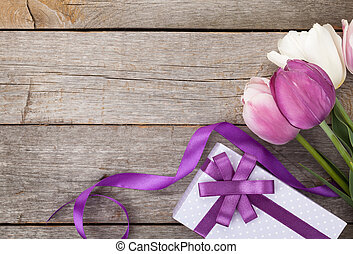 Fresh tulips with gift box over wooden table with copy space