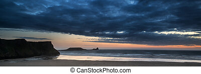 Landscape panorama Rhosilli Bay beach at sunset with moody...