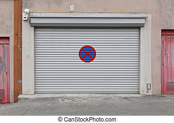 No parking - Gray garage door with no parking sign