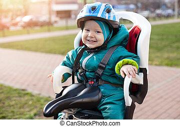 Little boy in a bike seat