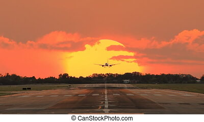airplane landing across the sun - airplane landing at...