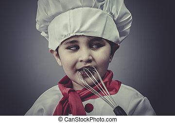 boy dressed as a cook with kitchen utensils
