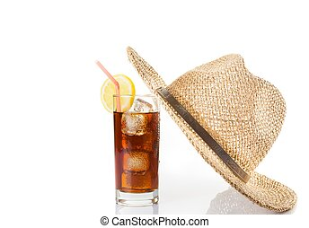 glass of fresh coke with straw near summer hat on top, summer time