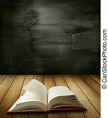 Book - Open book on table in front of blackboard