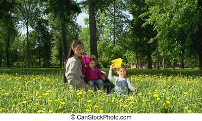 In the Bloom - Pan of young woman playing with her children...