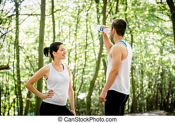 Couple resting after jogging - Young couple relaxing after...