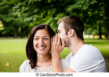 Tell me secret - whisper - Young man whispering to woman -...