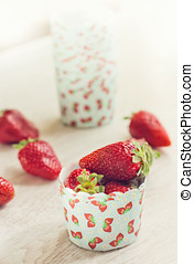 Fresh ripe strawberries on a paper case with pattern