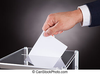 Businessman Inserting Ballot In Box On Desk - Cropped image...