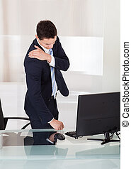 Businessman Suffering From Shoulder Ache In Office