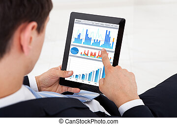 Businessman Comparing Graphs On Digital Tablet In Office -...
