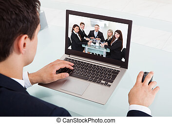 Businessman Video Conferencing On Laptop In Office - Cropped...