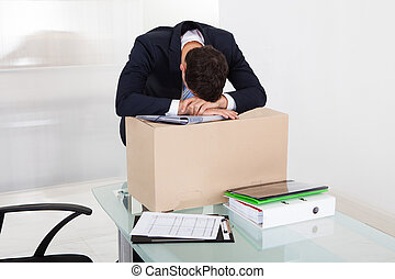 Tired Businessman Resting On Cardboard Box At Desk - Tired...