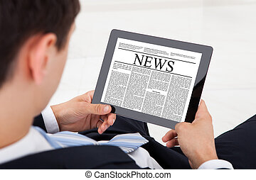Businessman Reading News On Digital Tablet In Office - High...