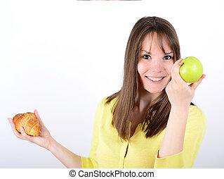 Doubtful woman holding an apple and croissant made right choice