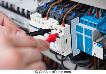 Electrician Examining Fusebox With Multimeter Probe -...