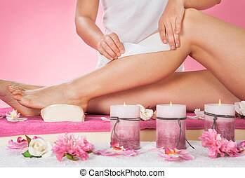 Therapist Waxing Customers Leg At Spa - Midsection of female...