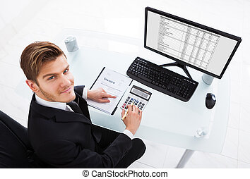 Businessman Calculating Expenses At Office Desk