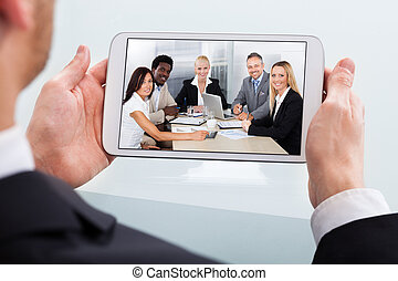 Businessman Video Conferencing On Digital Tablet At Desk -...