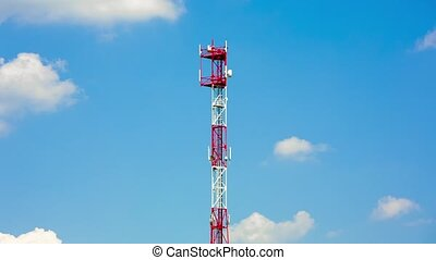 Telecommunications tower with parabolic antennas over a blue...