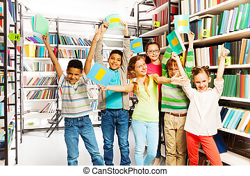 Happy children with hands up hold exercise books - Happy...