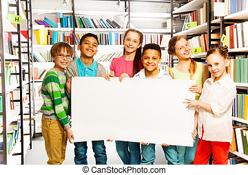 Friends holding white paper sheet in library - Happy friends...