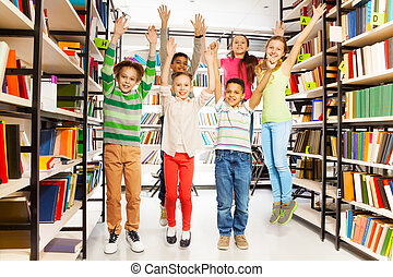Happy kids jumping with hands up in the library and standing...