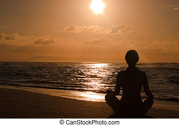 Female meditating on the beach at sunrise - Female...