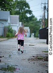running in puddles - Little girl runs away from the camera,...