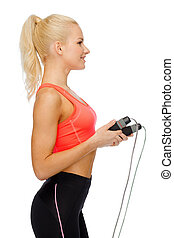 smiling sporty woman with with skipping rope - sport,...